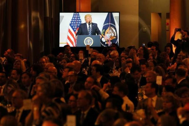 Guests listen as U.S. President Donald Trump delivers remarks at the National Republican Congressional Committee March Dinner in Washington, U.S., March 21, 2017. REUTERS/Carlos Barria