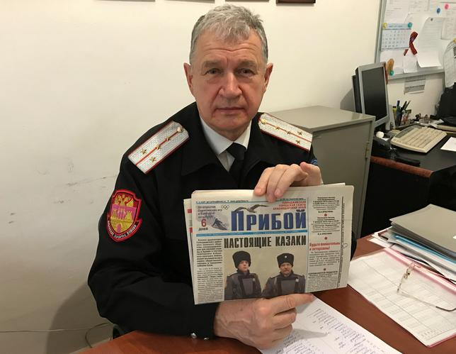 Russian Cossack commander Vladimir Bagliy shows a local newspaper with a picture of his fellow Cossack Yuri Sokalsky (R) killed near the Syrian city of Palmyra, in the Black Sea town of Gelendzhik, Russia, March 16, 2017.  REUTERS/Maria Tsvetkova