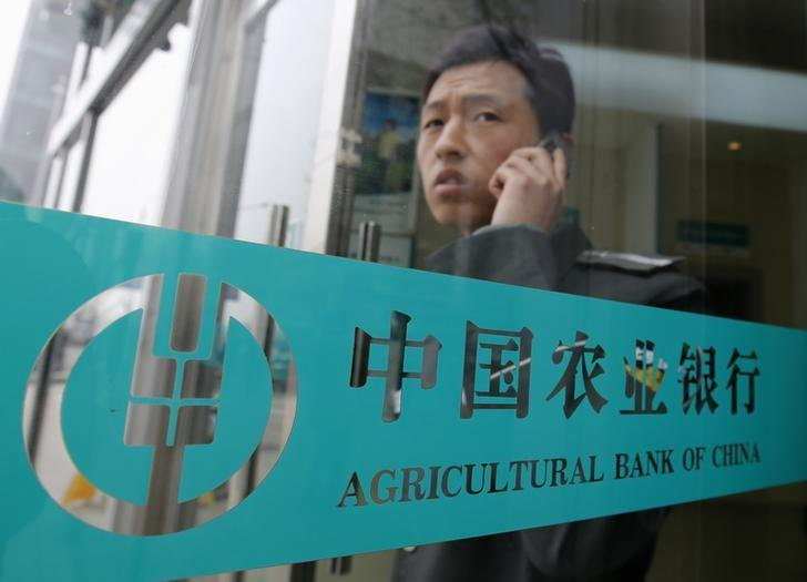 A man talks on a mobile phone while seen behind a logo of Agricultural Bank of China as he walks out of the bank in Beijing April 23, 2013. REUTERS/Kim Kyung-Hoon/Files
