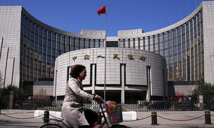 资料图片:一名女子骑车路过中国央行总部。REUTERS/Petar Kujundzic