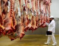Un mayorista inspecciona carcasas de res que cuelgan dentro de una habitación refrigerada en el matadero de Cibevial. en Corbas, Francia, el 4 de mayo de 2016. Algunos de los mayores proveedores de alimentos de China retiraron de sus estanterías la carne de vacuno y de pollo brasileña, en la primera señal concreta de que el escándalo que golpea a la industria procesadora de carne de Brasil está afectando los negocios en su principal mercado de exportación. REUTERS/Robert Pratta - RTX2CT9N