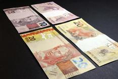 Imagen de archivo de unos billetes de 10 y 20 reales en el Banco Central de Brasil en Brasilia, jul 23, 2012. El Gobierno de Brasil recortó su estimación del crecimiento económico en 2017 a un 0,5 por ciento desde un 1 por ciento estimado anteriormente, informó el miércoles el Ministerio de Hacienda, una revisión que llevaría a que se congele el presupuesto y a una alza en los impuestos más tarde en el día.    REUTERS/Cadu Gomes (BRAZIL - Tags: BUSINESS)