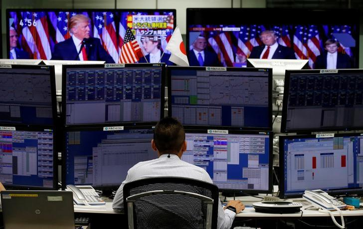 An employee of a foreign exchange trading company works near monitors showing U.S. President-elect Donald Trump speaking on TV (top) in Tokyo, Japan, November 9, 2016.   REUTERS/Toru Hanai/File Photo