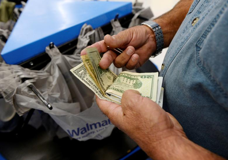 FILE PHOTO: A customer counts his cash at the checkout lane of a Walmart store in the Porter Ranch section of Los Angeles November 26, 2013.   REUTERS/Kevork Djansezian/File Photo