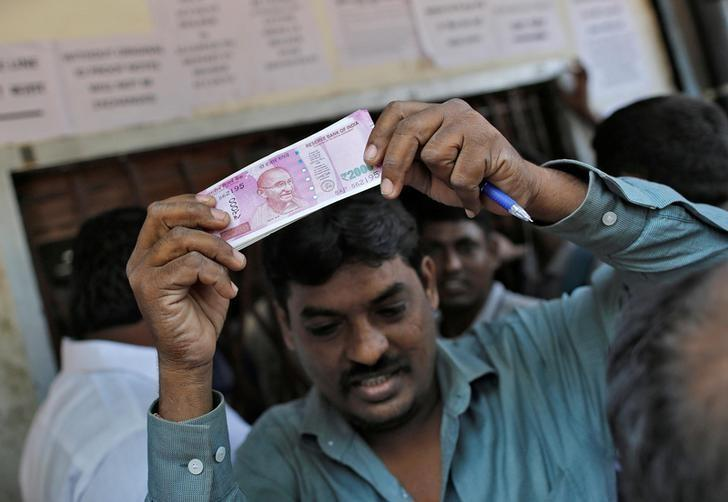 A man holds 2000 Indian rupees notes as he gets out of a bank in Mumbai, India, November 24, 2016. REUTERS/Danish Siddiqui/Files