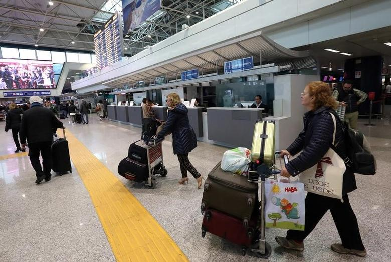 Travellers carry their luggages in the terminal at the Fiumicino's International airport near Rome, Italy, March 23, 2016. REUTERS/Stefano Rellandini