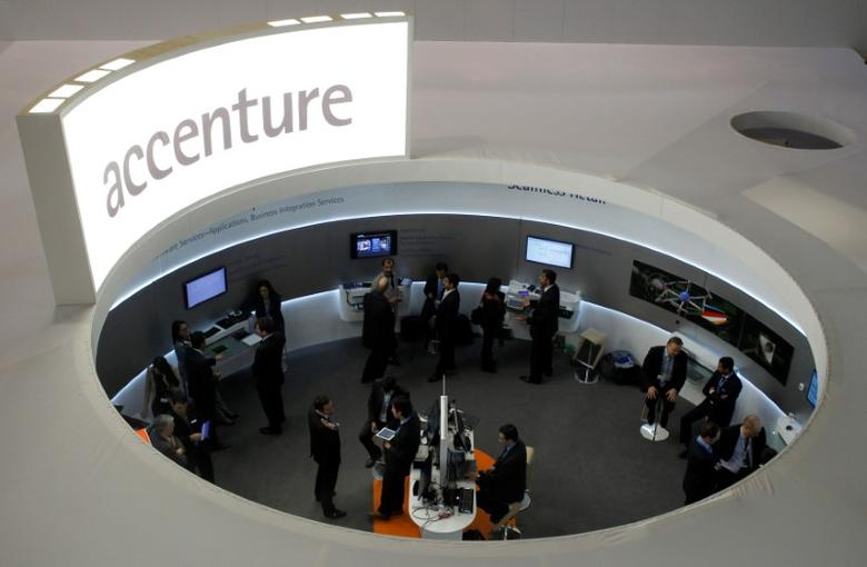 Visitors look at devices at Accenture stand at the Mobile World Congress in Barcelona, February 26, 2013.    REUTERS/Albert Gea/File Photo