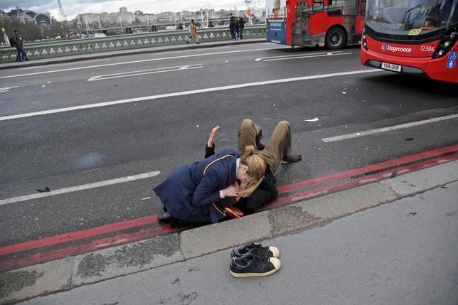 3月22日、「ドシンという鈍い衝撃音がして振り向くと、9メートルほど離れたところに男性が倒れていた」と、ロイターのカメラマン、トビー・メルビル記者は、英ロンドンの国会議事堂付近で発生した襲撃事件で、ウェストミンスター橋から下の歩道に男性が落ちたときの状況をこう語った。写真は橋の上で負傷者を助ける女性(2017年 ロイター/Toby Melville)