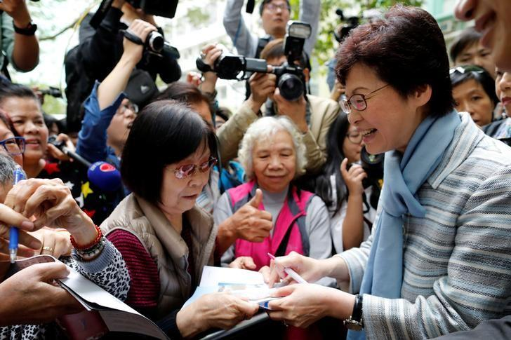 Chief Executive election candidate and former Chief Secretary Carrie Lam signs autographs for supporters during an election campaign in Hong Kong, China March 23, 2017. REUTERS/Tyrone Siu
