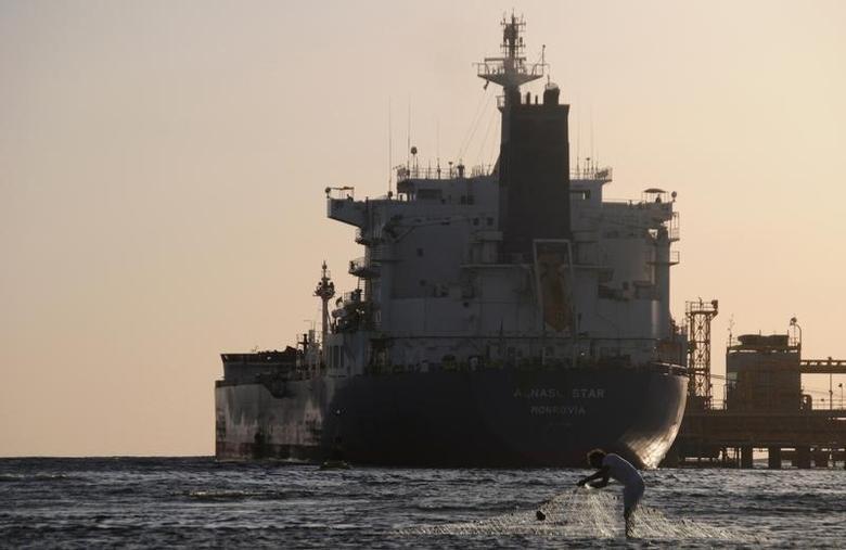 资料图片:2013年4月,沙特阿拉伯杜巴港口的油轮,一名渔民在附近收网。REUTERS/Mohamed Al Hwaity