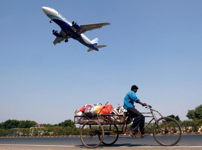 An IndiGo Airlines aircraft prepares to land as a man paddles his cycle rickshaw in Ahmedabad, India, October 26, 2015. REUTERS/Amit Dave/Files