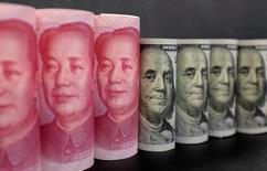 """Imagen de archivo de billetes de 100 dólares y billetes de 100 yuanes en Pekín, China . 21 de enero 2016. Los riesgos de insolvencias en China están """"muy controlados"""", pero los gobiernos locales deben asegurarse de que el aumento de su gasto de deuda durante este año esté dentro de los límites estipulados, dijo el viernes el ministro de Finanzas, Liu Wei. REUTERS/Jason Lee/Illustration/File Photo"""