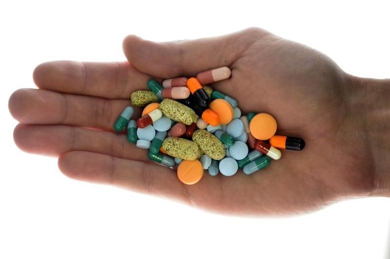 A person holds pharmaceutical tablets and capsules in this picture illustration taken in Ljubljana September 18, 2013.  REUTERS/Srdjan Zivulovic/Files