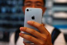 Imagen de un hombre sosteniendo su nuevo iPhone 7 en una tienda Apple en Pekín, China. 16 de septiembre, 2016. Un tribunal de China se pronunció a favor de Apple en una disputa de patentes de diseño entre el gigante tecnológico y un fabricante local de teléfonos, anulando la prohibición de venta contra el iPhone 6 y iPhone 6 Plus en el país, informó la agencia de noticias Xinhua. REUTERS/Thomas Peter