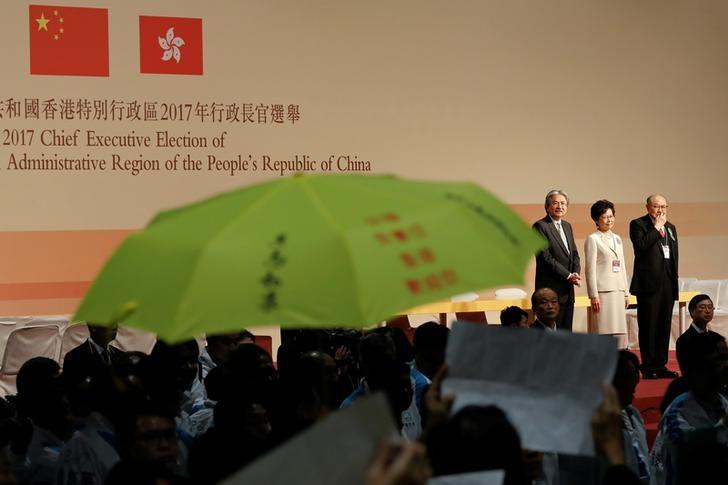 A yellow umbrella, the symbol of the Occupy Central movement, is displayed before candidates John Tsang, Carrie Lam and Woo Kwok-hing (L-R) as Lam is announced the winner of the election for Hong Kong's Chief Executive in Hong Kong, China March 26, 2017.   REUTERS/Tyrone Siu