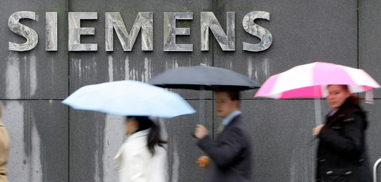 People covered with umbrellas walk next to a Siemens building in Munich, Germany, November 13, 2008.  REUTERS/Michaela Rehle/File Photo