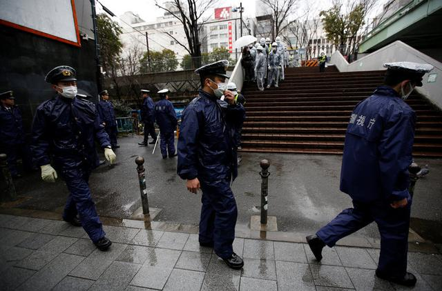 Police officers walk as they guard inside the barricade fences at a gate of Miyashita park in Tokyo, Japan March 27, 2017.   REUTERS/Issei Kato