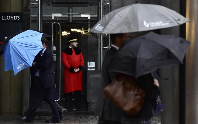 A doorman looks out as workers walk in the rain past the Lloyd's of London building in the City of London, Britain, January 7, 2016. Britain's finance minister George Osborne said on Thursday that Britain's economy was not immune from a ''dangerous cocktail'' of threats from abroad, and urged against complacency after two years of solid growth. REUTERS/Toby Melville - RTX21F4L