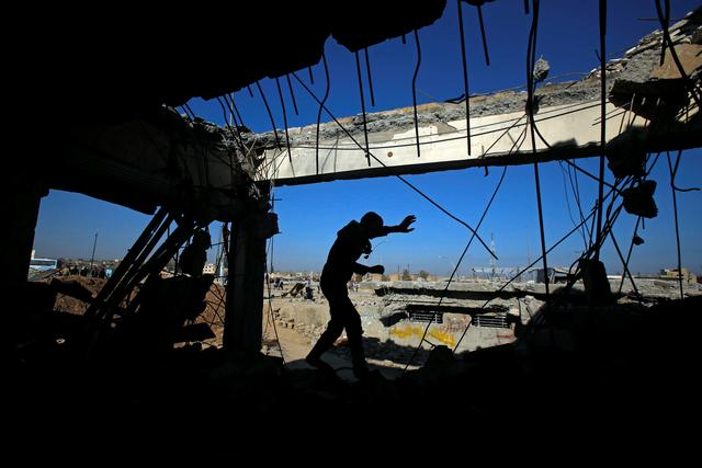 REFILE - ADDING DETAILS OF LOCATION   An Iraqi runs through a destroyed building as Iraqi forces battle with Islamic State militants, in the Somod neighbourhood in western Mosul, Iraq March 27, 2017. REUTERS/Suhaib Salem     TPX IMAGES OF THE DAY