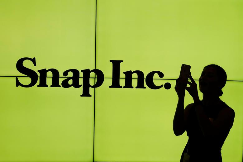 A woman stands in front of the logo of Snap Inc. on the floor of the New York Stock Exchange (NYSE) while waiting for Snap Inc. to post their IPO, in New York City, NY, U.S. March 2, 2017. REUTERS/Lucas Jackson