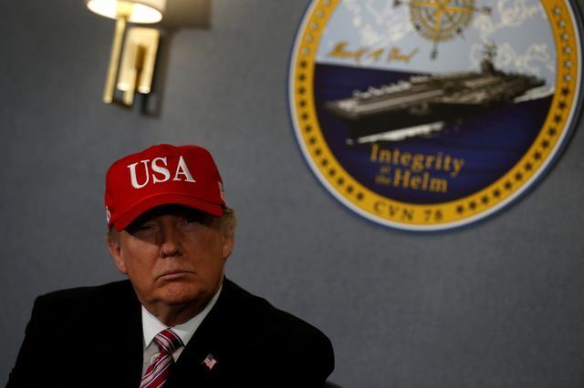 3月2日、トランプ米大統領は、国防支出の増額計画を自画自賛する演説の舞台として、建造に約1兆5000億円を費やした米海軍の最新鋭航空母艦「ジェラルド・R・フォード」の甲板を選んだ。写真は米バージニア州で、空母での演説前にブリーフィングを受ける同大統領(2017年 ロイター/Jonathan Ernst)