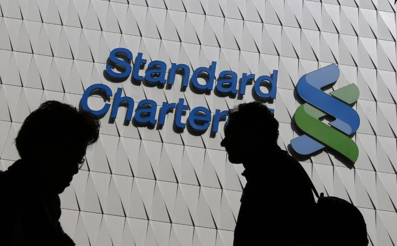 Passersby walk in front of the main branch of Standard Chartered in Hong Kong, in this January 8, 2015 file photo.  REUTERS/Bobby Yip