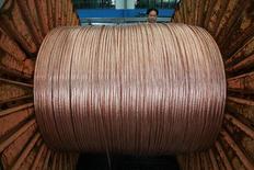 Un empleado mira el rollo de cable de cobre en la provincia de Jiangsu, China. 24 de julio 2006.Las principales fundiciones de cobre de China acordaron recortar a un 11 por ciento en el segundo trimestre sus tarifas de procesamiento y refinación, luego de las interrupciones en la extracción de los dos mayores yacimientos del mundo que afectaron el suministro global del metal, dijeron fuentes el martes. © STR New / Reuters