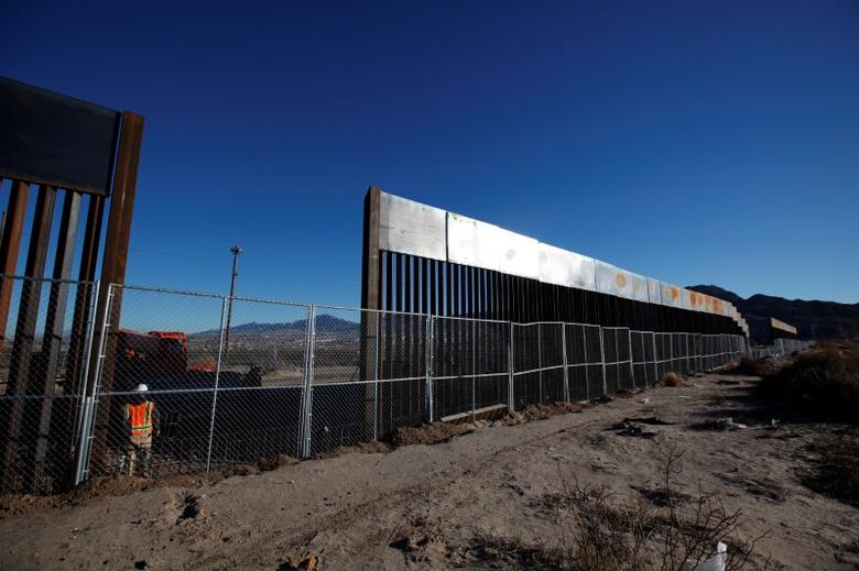 A worker stands next to a newly built section of the U.S.-Mexico border fence at Sunland Park, U.S. opposite the Mexican border city of Ciudad Juarez, Mexico January 25, 2017. Picture taken from the Mexico side of the U.S.-Mexico border. REUTERS/Jose Luis Gonzalez