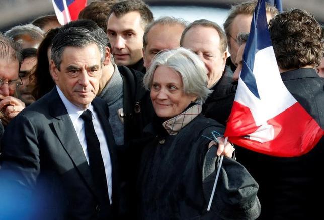 3月28日、フランス大統領選の中道・右派統一候補であるフィヨン元首相(左)の妻ペネロプ夫人(中央右)が議員秘書として給与を不正に受け取っていたとされる問題で、予審判事は28日、夫人に対する予審を開始した。写真はパリで5日撮影(2017年 ロイター/Philippe Wojazer )