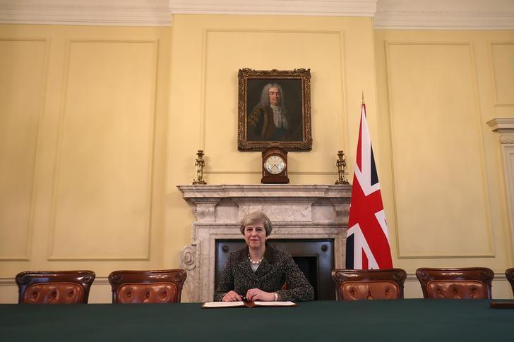 British Prime Minister Theresa May in the cabinet, sitting below a painting of Britain's first Prime Minister Robert Walpole, signs the official letter to European Council President Donald Tusk invoking Article 50 and the United Kingdom's intention to leave the EU on March 28, 2017 in London, England. REUTERS/Christopher Furlong/Pool