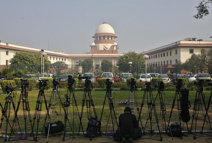 FILE PICTURE: A television journalist sets his camera inside the premises of the Supreme Court in New Delhi February 18, 2014.  REUTERS/Anindito Mukherjee