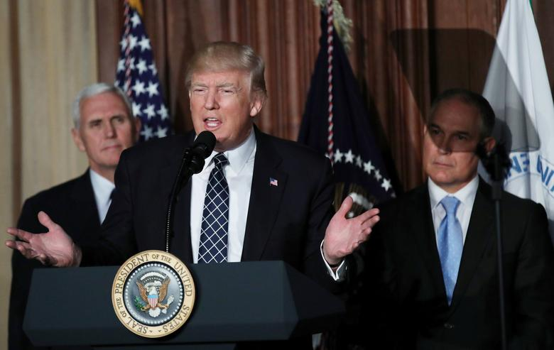 U.S. President Donald Trump speaks between Vice President Mike Pence (L) and EPA Administrator Scott Pruitt prior to signing an executive order on ''energy independence,'' eliminating Obama-era climate change regulations, during an event at the Environmental Protection Agency (EPA) headquarters in Washington, U.S., March 28, 2017. REUTERS/Carlos Barria