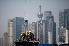 Un grupo de operarios trabaja en una obre frente al distrito financiero de Pudong, en Shangái, China. 27 marzo 2017. La economía de China, la segunda más grande del mundo, crecerá probablemente un 6,8 por ciento en el primer trimestre del año, dijo el miércoles la agencia oficial de noticias Xinhua citando a un grupo de expertos del Gobierno. REUTERS/Aly Song