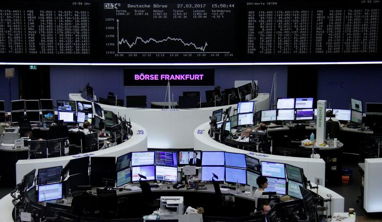 Traders work at their desks in front of the German share price index, DAX board, at the stock exchange in Frankfurt, Germany, March 27, 2017. REUTERS/Staff/Remote
