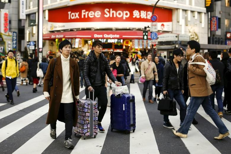 FILE PHOTO: People cross a street outside a tax-free department store popular among Chinese tourists in Tokyo, Japan, February 11, 2016. Picture taken February 11, 2016. REUTERS/Thomas Peter/File Photo