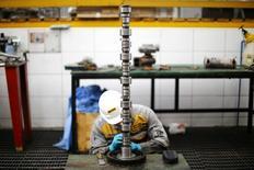 Un trabajador inspecciona una pieza de un camión de minería, en Santiago, Chile. 9 de marzo 2016. La producción industrial en Chile se contrajo un 7,6 por ciento en febrero, presionada por un negativo desempeño de la minería y las manufacturas, en medio de una persistente débil economía, dijo el jueves el Gobierno.  REUTERS/Ivan Alvarado  - RTSDU9R