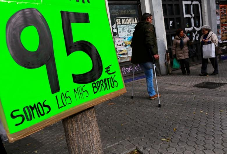 People walk past a placard with a price and words reading ''We are the cheapest'' outside a shop in the Andalusian capital of Seville December 12, 2014.  REUTERS/Marcelo del Pozo/File Photo