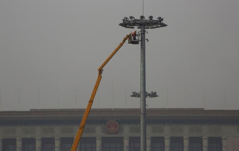 A worker maintains a street light at Tiananmen Square among smog during a polluted day in Beijing, China, January 6, 2017. REUTERS/Jason Lee
