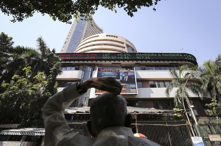 A man looks at a screen across the road displaying the Sensex on the facade of the Bombay Stock Exchange (BSE) building in Mumbai February 17, 2014.  REUTERS/Danish Siddiqui/File Photo