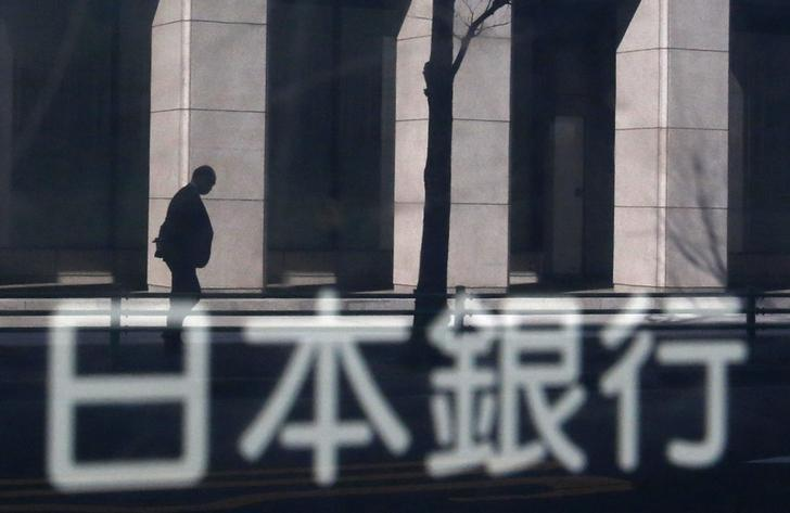 资料图片:2014年1月,日本央行大楼标志牌映出的路过一栋大楼的男子。REUTERS/Yuya Shino