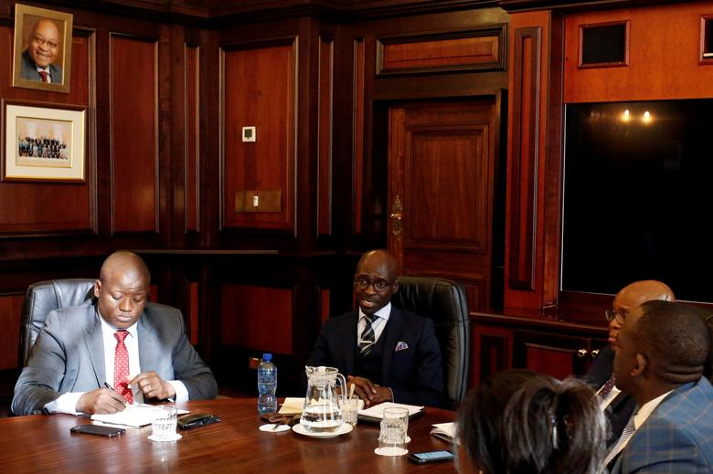 FILE PHOTO: South Africa's new finance minister, Malusi Gigaba (2nd R) speaks with members of the treasury during his visit to their offices in Pretoria, South Africa, March 31,2017. REUTERS/Siphiwe Sibeko/File Photo