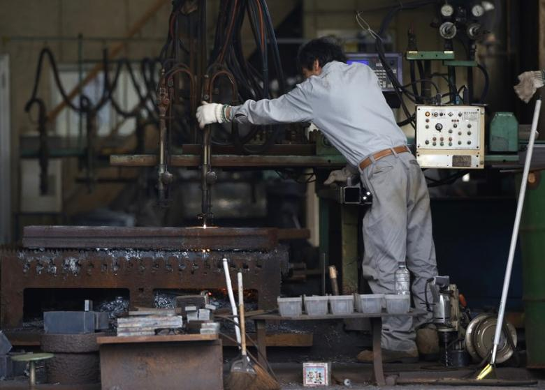 FILE PHOTO - A man works around a metal procession machine at a factory in Urayasu, east of Tokyo October 9, 2014. REUTERS/Issei Kato