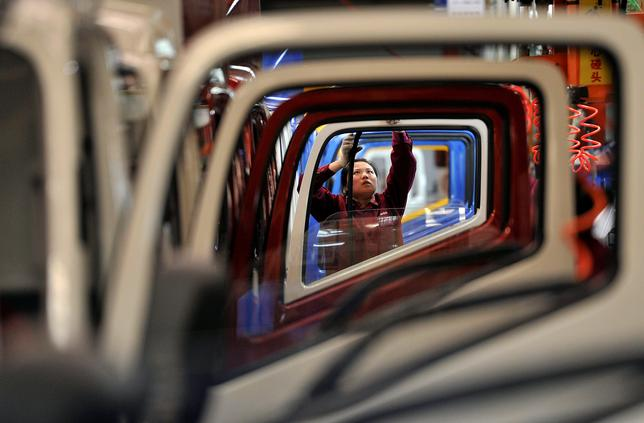 FILE PHOTO: A worker installs rubber onto the windows of the doors along a production line at a truck factory of Anhui Jianghuai Automobile Co. Ltd (JAC Motors) in Hefei, Anhui province May 5, 2014.   REUTERS/Stringer/File Photo
