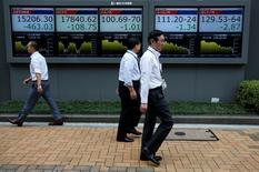 Peatones caminan frente a unas pantallas que muestra el índice Nikkei y otras divisas afuera de una correduría en Tokio, Japón. 6 de julio de 2016. El índice Nikkei de la bolsa de Tokio subió el lunes pero no logró recuperar completamente las pérdidas sufridas la semana pasada, luego de que un sondeo optimista del Banco de Japón no redujo las preocupaciones sobre las perspectivas de los exportadores. REUTERS/Issei Kato