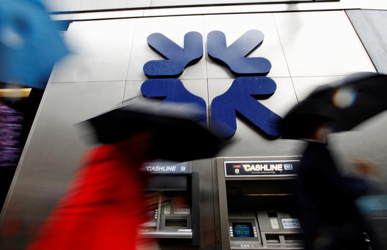FILE PHOTO: Morning commuters rush past a branch of the Royal Bank of Scotland (RBS) in London November 4, 2011.  REUTERS/Andrew Winning/File Photo