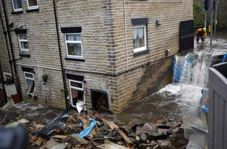 An emergency services worker stands in flood water as he helps to clear the flooding in Stalybridge, Britain November 22, 2016.  REUTERS/Phil Noble