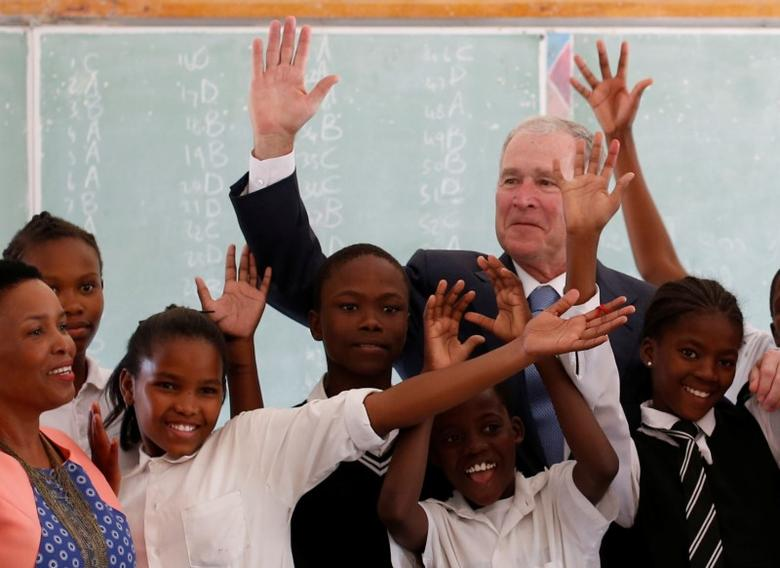 Former US President George W. Bush poses for a photograph with children at a school in Gaborone, Botswana, April 4, 2017.  REUTERS/Mike Hutchings
