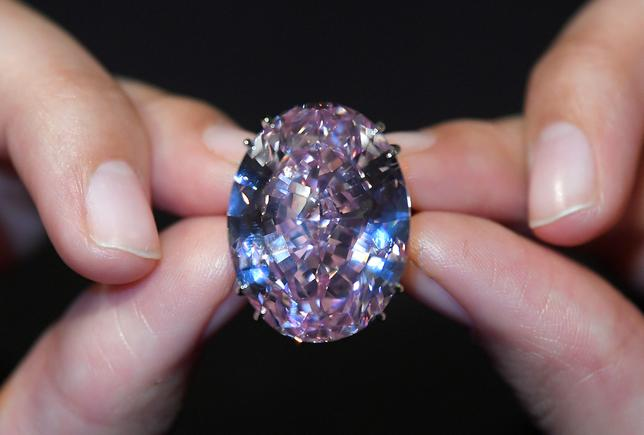 FILE PHOTO: A model poses with a 59.60-carat mixed cut diamond known as ''The Pink Star'', the largest Internally Flawless Fancy Vivid Pink diamond ever graded by the Geological Institute of America (GIA), ahead of being auctioned in Hong Kong by Sotheby's. REUTERS/Toby Melville/File Photo