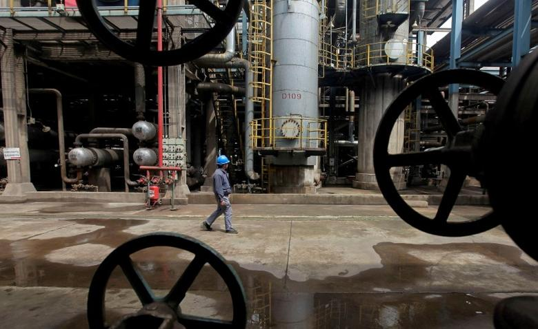 A worker walks past oil pipes at a refinery in Wuhan, Hubei province March 23, 2012. REUTERS/Stringer/File Photo