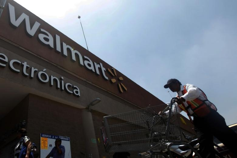 A worker moves a shopping cart outside a Wal-Mart store in Mexico City, August 15, 2012.   REUTERS/Edgard Garrido